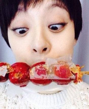 照片中,孙俪一脸素颜,张大嘴巴不顾形象的吃着诱人的糖葫芦,最为夸