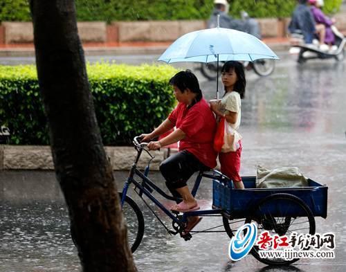 昨日上午,晋江市标,女儿给骑三轮车的妈妈撑伞,行